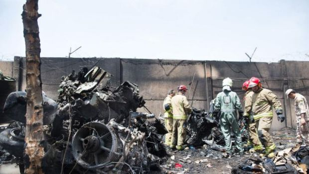 Rescuers sift through the wreckage of the plane that crashed, killing at least 38 people.