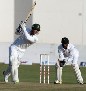 Quinton de Kock in action as Zimbabwe wicket keeper Richmond Mutumbami looks on.