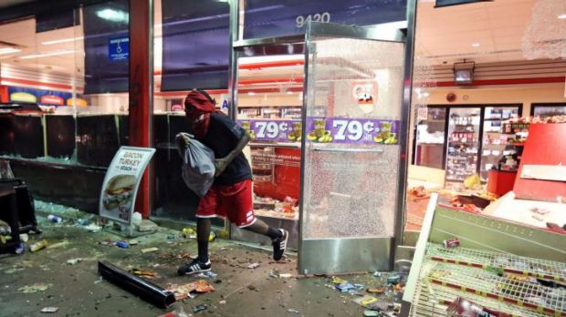 Looting ... A man leaves a store with a bag of goods after a protest turned into rioting in Ferguson, Missouri.