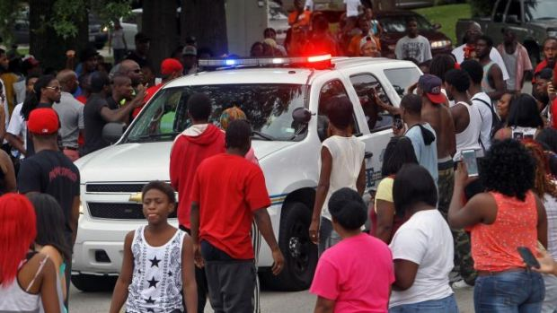 Protesters bang on the side of a police car Sunday evening in Ferguson, Missouri.