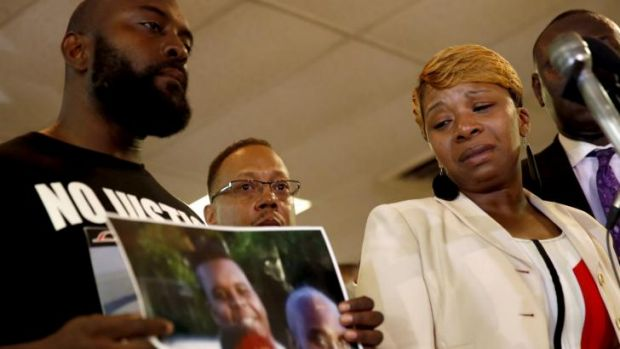 Lesley McSpadden (right) the mother of Michael Brown, with Mr Brown's father, Michael Brown snr holding a photo of their ...