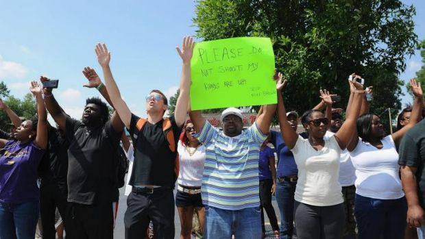 'Don't shoot': protesters confront police in St Louis after Michael Brown was shot.