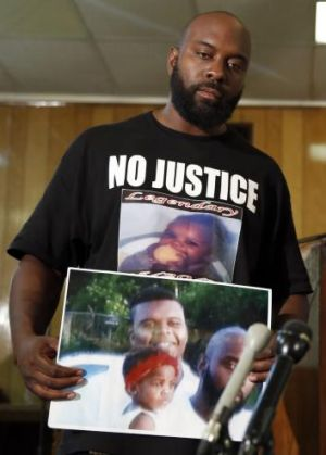 Michael Brown snr holds up a photo of himself with his son, Michael Brown.