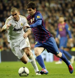 Real Madrid's Pepe with Barcelona's Lionel Messi.
