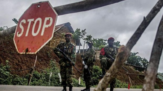 Soldiers stand guard at a roadblock outside Kenema, Sierra Leone.