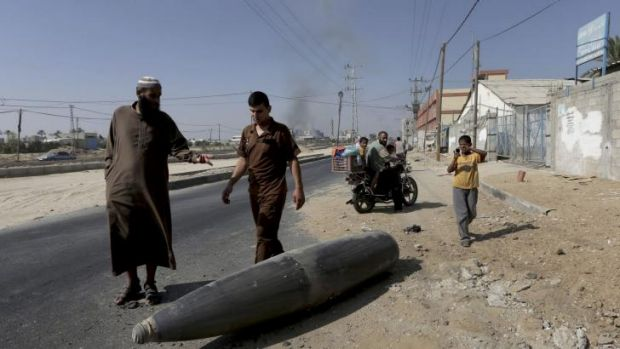 Palestinian onlookers pause to inspect an unexploded shell from the Israeli military lying on the main road in Deir ...