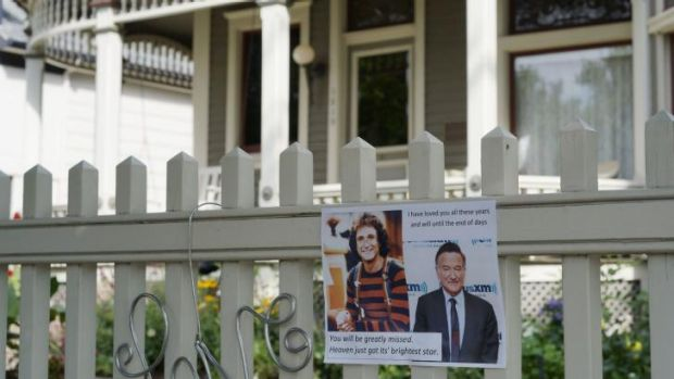 A photo of Robin Williams' Mork character is left at an impromptu memorial set up outside the house used in his breakout ...