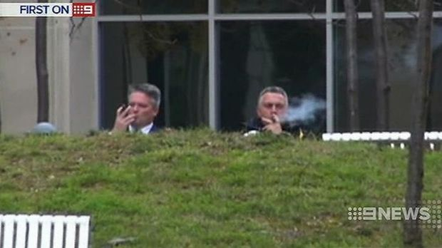 Finance Minister Mathias Cormann and Treasurer Joe Hockey enjoy cigars outside The Treasury in Canberra during budget ...