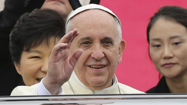 Pope Francis waves upon his arrival at Seoul Air Base as South Korean President Park Geun-hye (left) looks on.