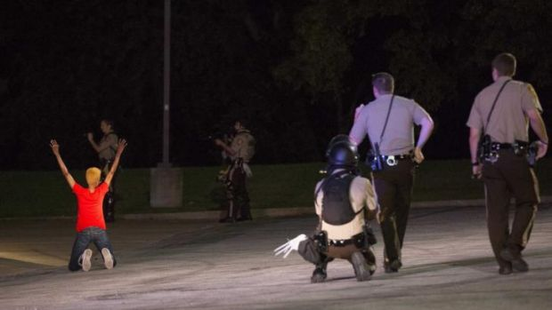 Police officers briefly detain a person in Ferguson on Wednesday.