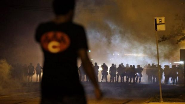 A man watches as police walk through a cloud of smoke during a clash with protesters on Wednesday, in Ferguson, Missouri.