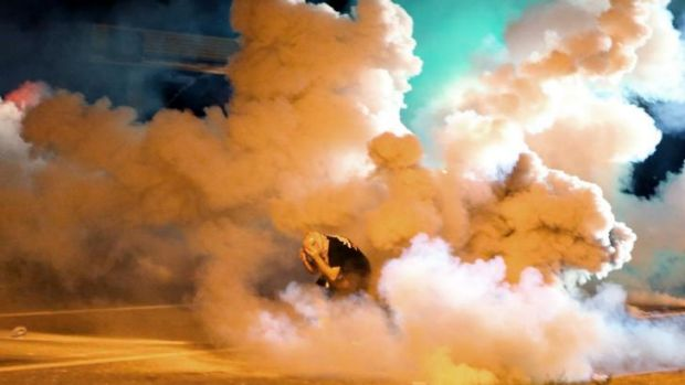 A protester takes shelter from a smoke bomb.