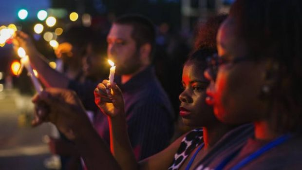 Protesters hold candles during a peaceful demonstration, as communities react to the shooting of Michael Brown in ...