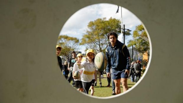 Matt Toomua gives some tips to children at a Wallabies fan day in Circular Quay on Thursday.