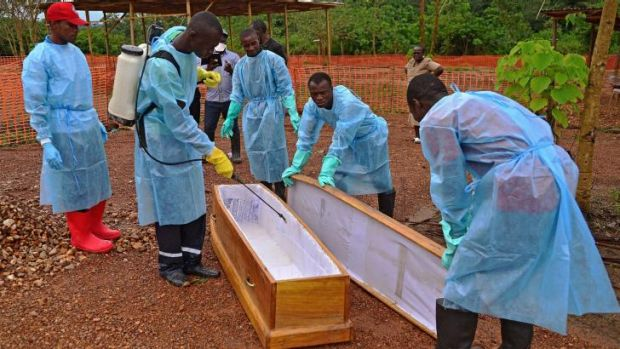 A Sierra Leone government burial team disinfects a coffin at the Medecins Sans Frontieres facility in Kailahun.