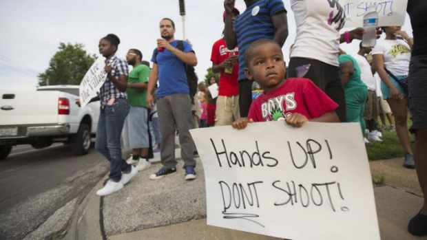 Romel Turner, 3, holds a sign during a peaceful demonstration at Great St Mark Family Church, as communities react to ...