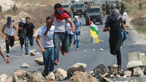 Palestinian protesters run for cover as Israeli soldiers fire rubber bullets after the demonstration.