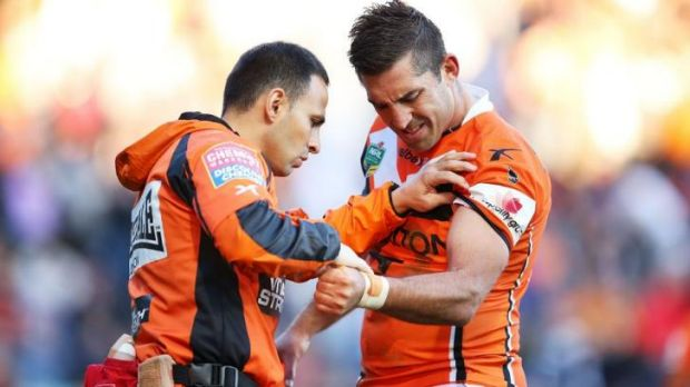 The end: Braith Anasta is attended to by a Tigers trainer during the clash with Penrith.
