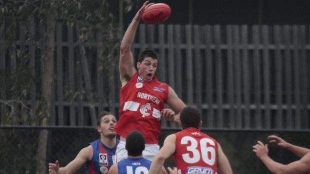 Matthew Kreuzer leaps up to punch the ball.