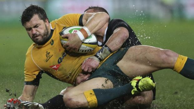 Mud bath: Adam Ashley-Cooper is taken to the turf by Aaron Cruden.