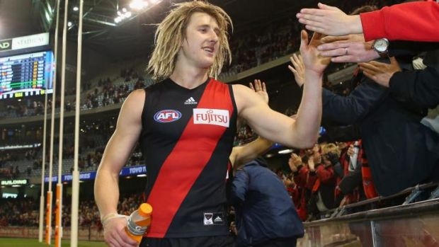 Dyson Heppell of the Bombers high-fives fans after the game.