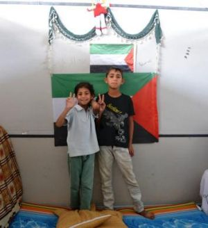 Ashjan, 9, and Marwan, 11, stand in front of a Palestinian flag in a cubicle at a camp for Syrian-based Palestinian ...