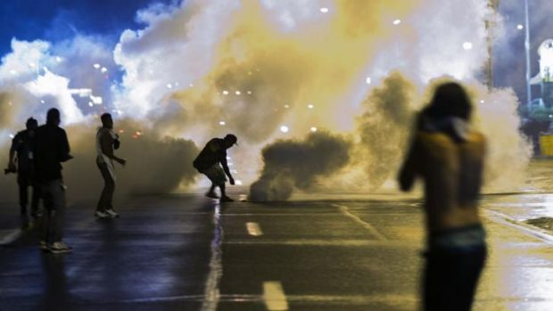 A protester reaches down to throw back a smoke canister as police clear a street after the curfew.