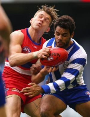 Daniel Wells of the Kangaroos (right) bumps Shaun Higgins of the Bulldogs at Etihad Stadium on Sunday.