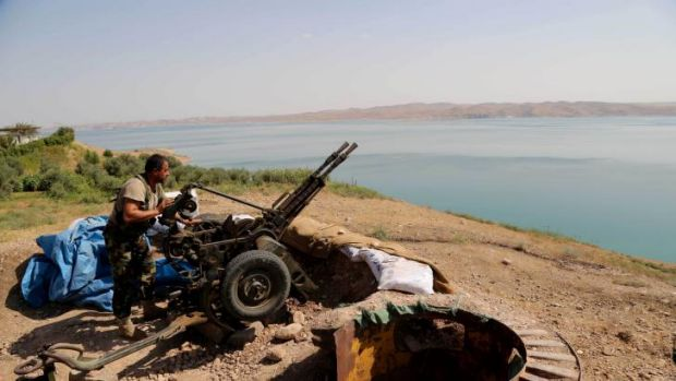 A Kurdish Peshmerga fighter prepares his weapon at his combat position near the Mosul Dam.