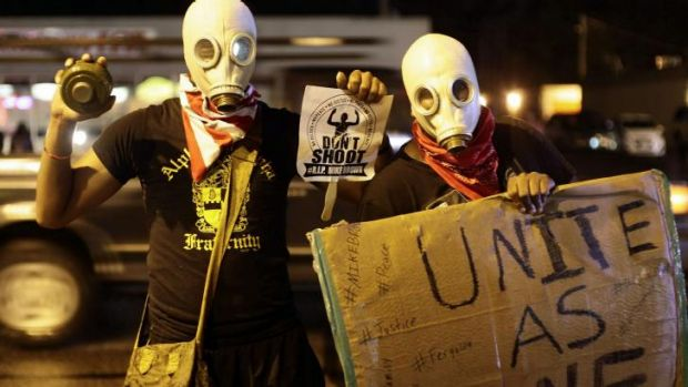 Masked demonstrators protest against the police shooting of 18-year-old Michael Brown by holding up signs on the streets ...