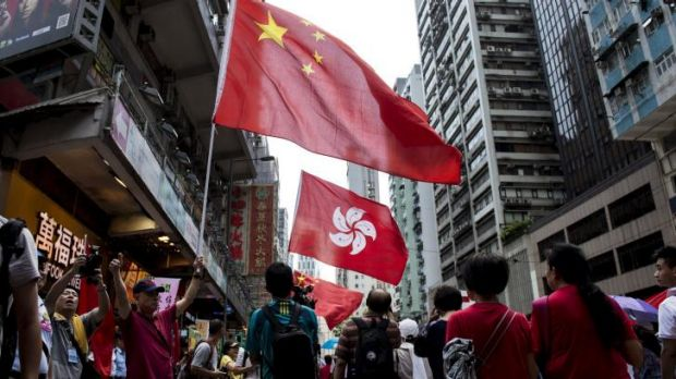 People hold the Chinese and Hong Kong flags as they take part in the demonstration.