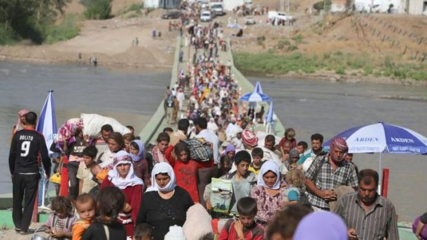 Displaced Iraqis from the Yazidi community cross the Syrian-Iraqi border.