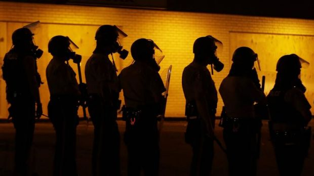 Police wait to advance on demonstrators after tear-gas was used to disperse a crowd on Sunday night in Ferguson, Missouri.