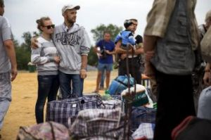 People displaced by fighting in Ukraine wait before boarding a bus, ahead of their journey by train to the Russian ...
