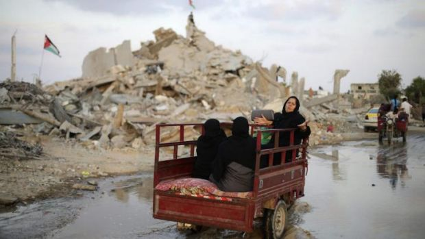 Palestinians in the ruins of houses in Khan Younis, Gaza.