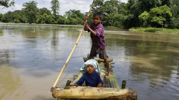 A boy rows a makeshift raft carrying a child through the flooded areas of Lakhimpur district in the north-eastern Indian ...