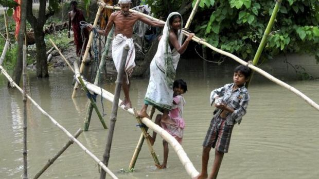Villagers use a bamboo structure to move across a flooded village in Morigaon district of north-eastern Assam state.