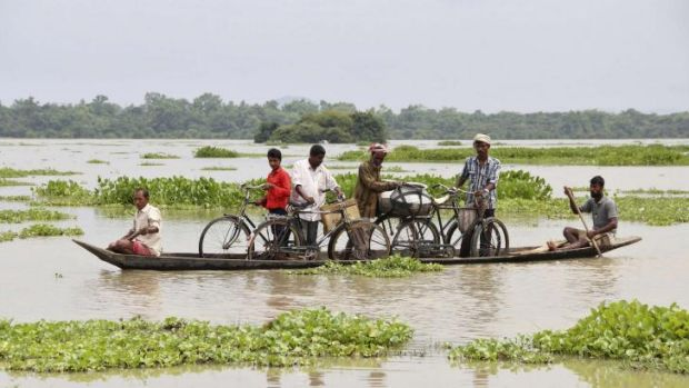 Villagers transport their bicycles on a boat through the flooded areas of Morigaon district in the north-eastern Indian ...