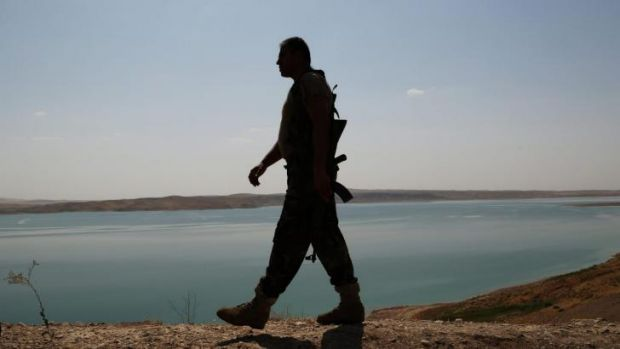 A Peshmerga fighter patrols near Mosul dam at the town of Chamibarakat.