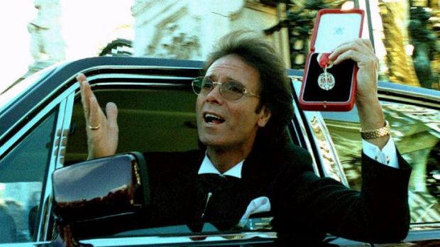 Celebrated: Cliff Richard is photographed at the gates of Buckingham Palace after receiving his knighthood from the ...