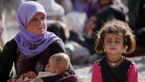 A Yazidi Iraqi woman sits with her children at the Bajid Kandala camp near the Tigris River in Kurdistan after fleeing ...