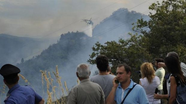 A helicopter sprays water on flames after two Italian air force fighter jets collided during a training mission over ...