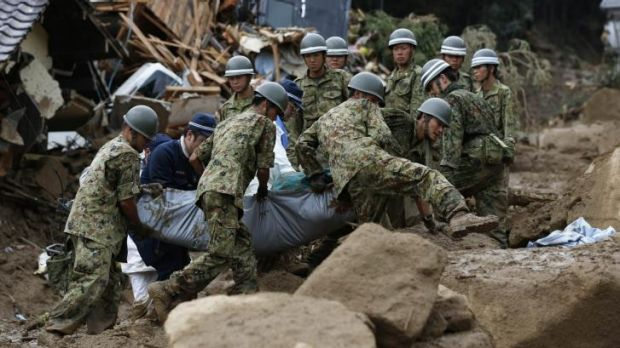 Japanese soldiers and police carry the body of a victim after the landslide swept through a residential area at ...
