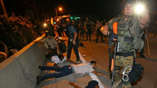 Police begin arresting dozens of protesters on West Florissant Avenue after they refused to leave the area and some ...
