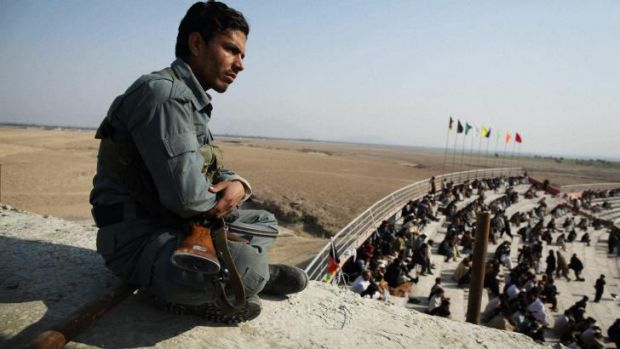 An Afghan policeman watches over the crowd at a match between Tajikistan and Afghanistan's A Team in Jalalabad.