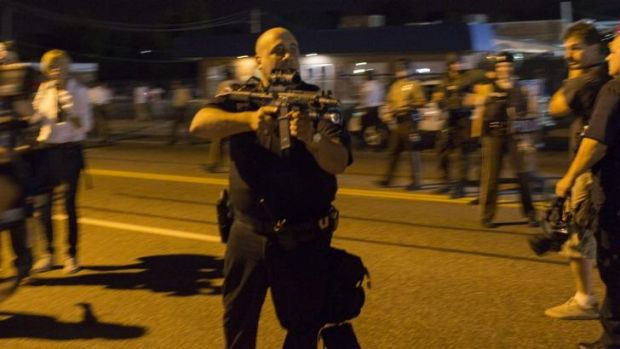 Missouri police officer Ray Albers points an assault rifle at a protester.