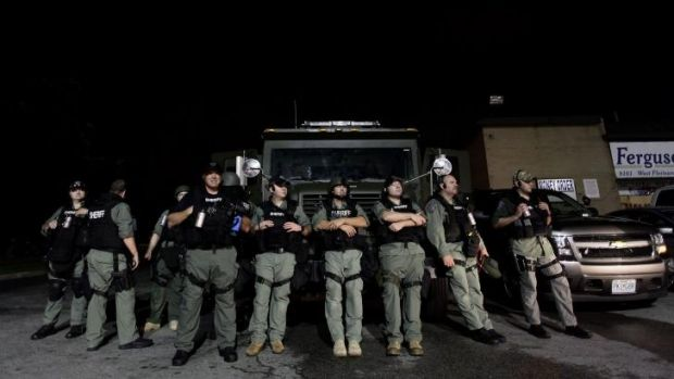 Police watch as demonstrators protest the shooting death of Michael Brown.