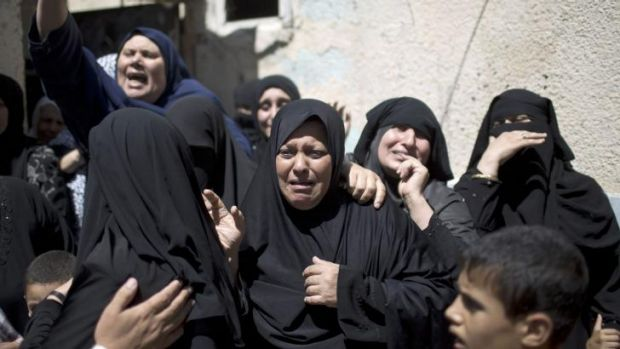 Relatives of senior Hamas commander Raed al-Atar mourn during his funeral.
