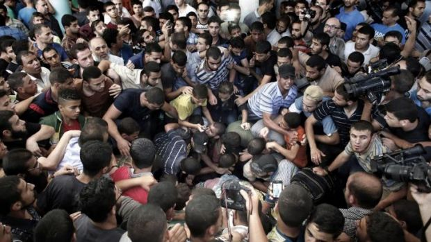 Palestinian Hamas supporters mourn over the body of one of three commanders.