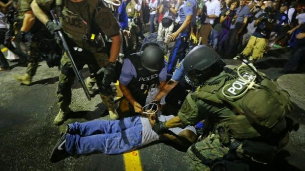 Baghdad or Missouri?: Khaki-clad police officers apprehend a man in Ferguson during this week's protests.